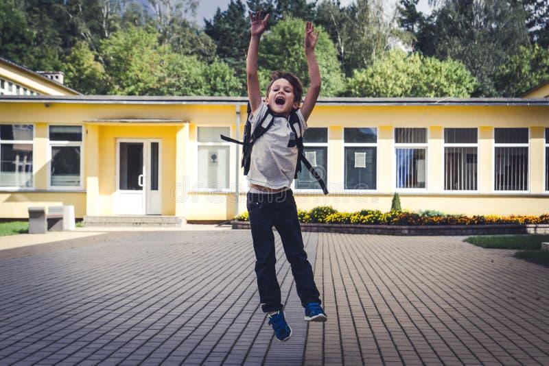 Gelukkige jongen met rugzak die en pret voor school springen hebben Appel en melk tegen een bord met terug naar schoolbericht op  stock fotografie