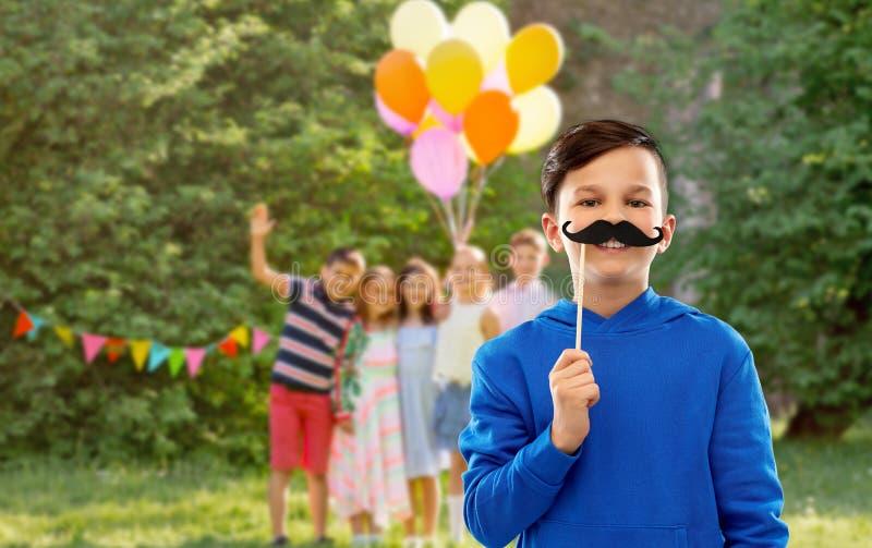 Gelukkige jongen met zwarte snorren bij verjaardagspartij royalty-vrije stock afbeeldingen