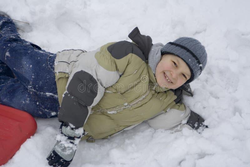 Gelukkige jongen op sneeuw stock fotografie