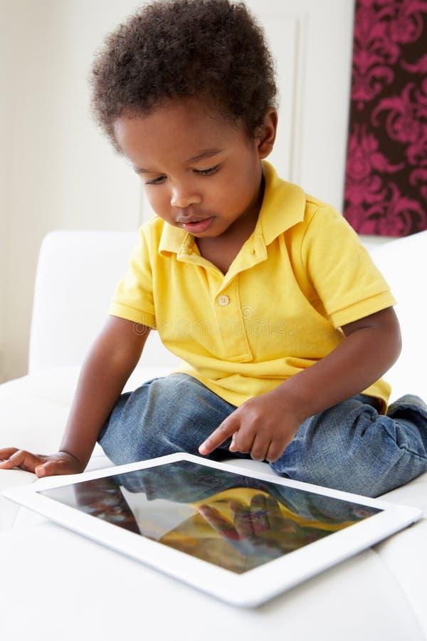 Gelukkige Jongen op Sofa Playing With Digital Tablet royalty-vrije stock afbeelding