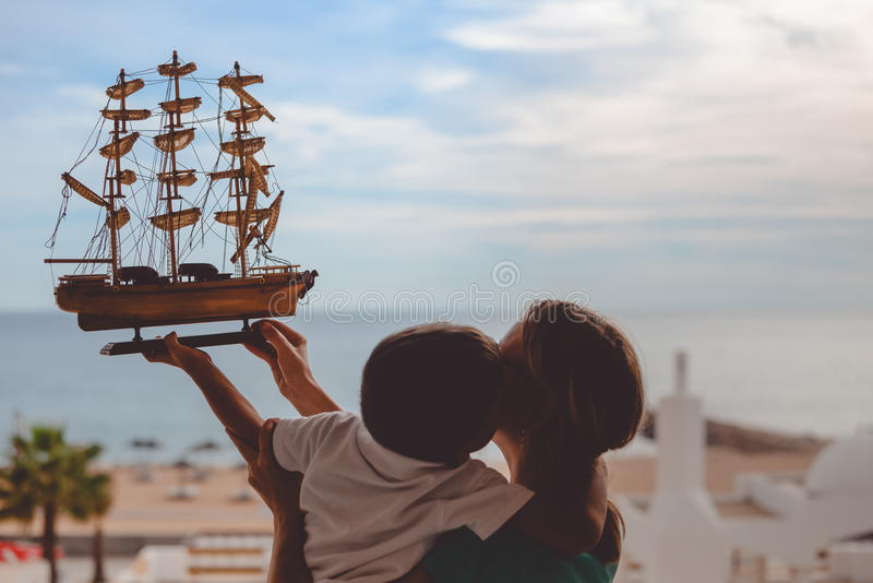 Gelukkige jongens kussende moeder en het houden van schipmodel stock fotografie