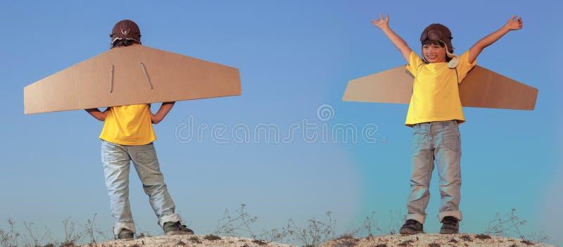 Gelukkige jongens met kartondozen van vleugels tegen hemeldroom van het vliegen stock foto's