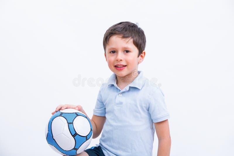 Gelukkige jongens speelvoetbal Leuk kind, jonge mannelijke tienerkeeper die sport van spel genieten Weinig geïsoleerde bal van de royalty-vrije stock afbeeldingen