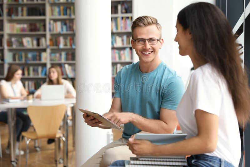Gelukkige jongeren die in bibliotheek spreken royalty-vrije stock foto's