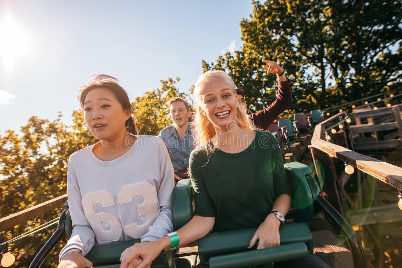 Gelukkige jongeren die een achtbaan berijden stock afbeeldingen