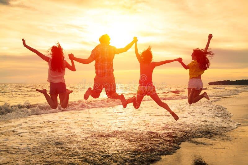 gelukkige jongeren die op het strand springen royalty-vrije stock foto's