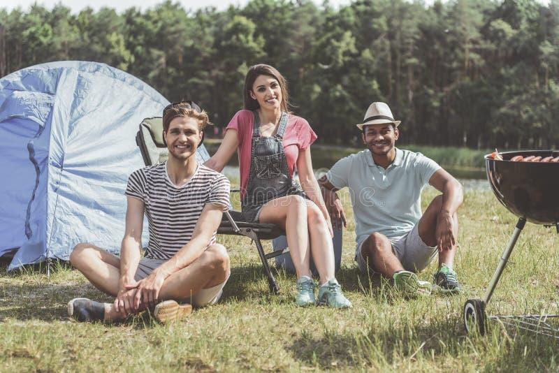 Gelukkige jongeren die in openlucht rusten stock fotografie