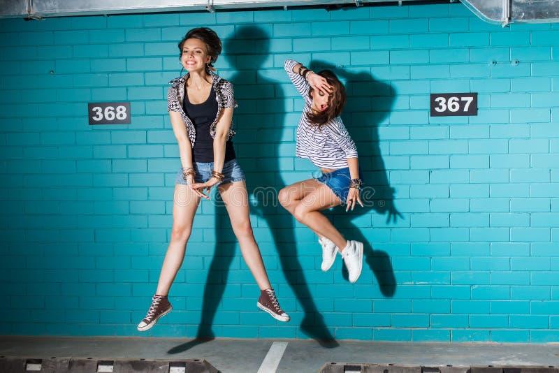 Gelukkige jongeren die pret hebben en voor blauwe baksteen springen stock fotografie