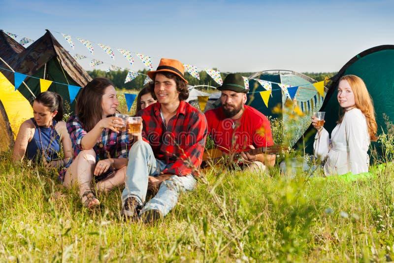 Gelukkige jongeren die samen bij kampeerterrein drinken royalty-vrije stock afbeelding