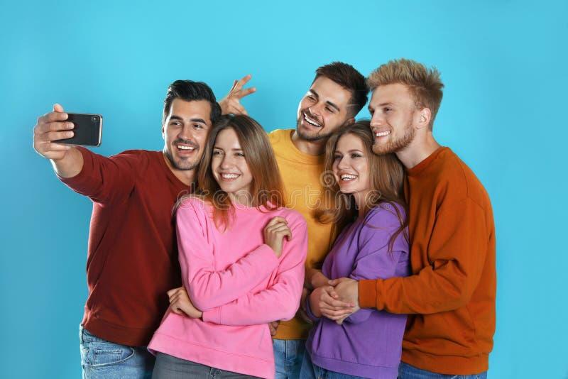 Gelukkige jongeren die selfie op blauw nemen stock fotografie