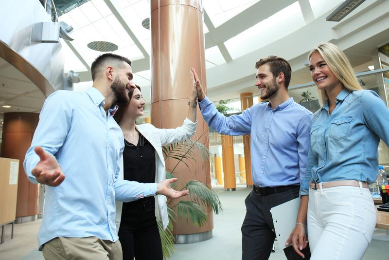 Gelukkige jongeren die zich in bureau bevinden en hoogte vijf geven aan hun collega's royalty-vrije stock foto's