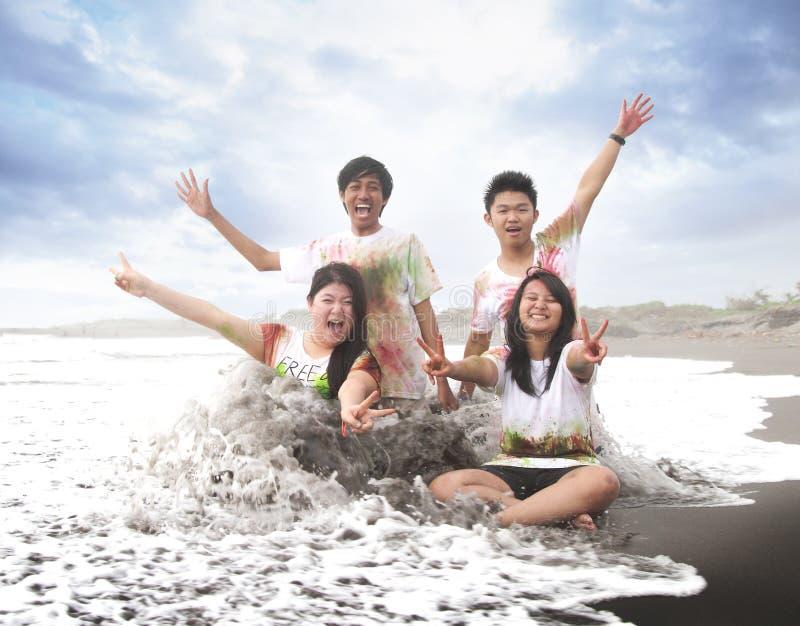 Gelukkige jongeren in een strand in de zomer met langzame motie en onscherp concept royalty-vrije stock fotografie