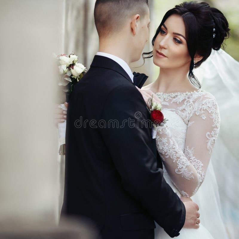 Gelukkige jonggehuwde donkerbruine bruid die knappe bruidegom koesteren dichtbij oude wa stock afbeeldingen