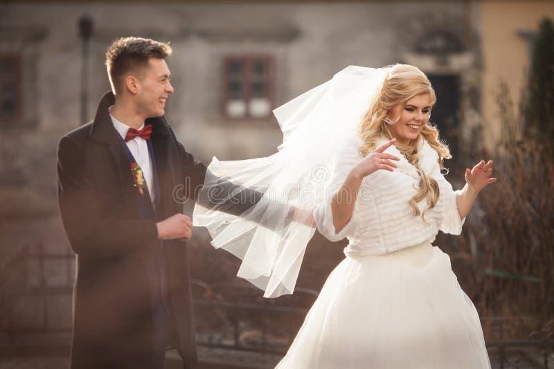 Gelukkige jonggehuwdebruidegom die blonde mooie bruid erachter koesteren van stock afbeeldingen