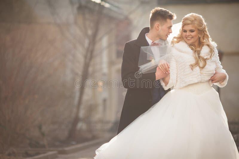 Gelukkige jonggehuwdebruidegom die blonde mooie bruid erachter koesteren van royalty-vrije stock foto's