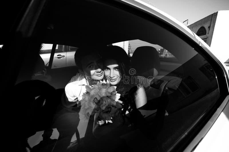Gelukkige jonggehuwden in de auto b&w stock afbeeldingen