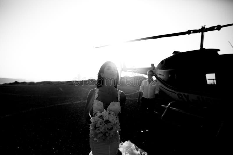 Gelukkige jonggehuwden dichtbij de helikopter stock afbeeldingen