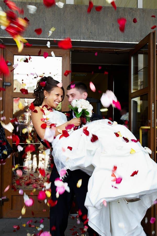 Gelukkige jonggehuwden en vliegende bloemblaadjes royalty-vrije stock foto