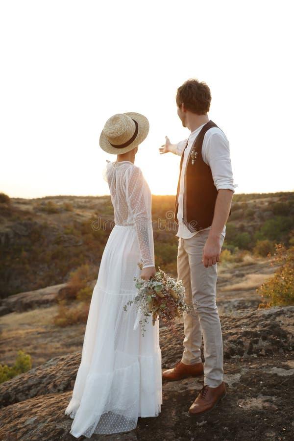 Gelukkige jonggehuwden met mooie gebiedsboeket status royalty-vrije stock fotografie