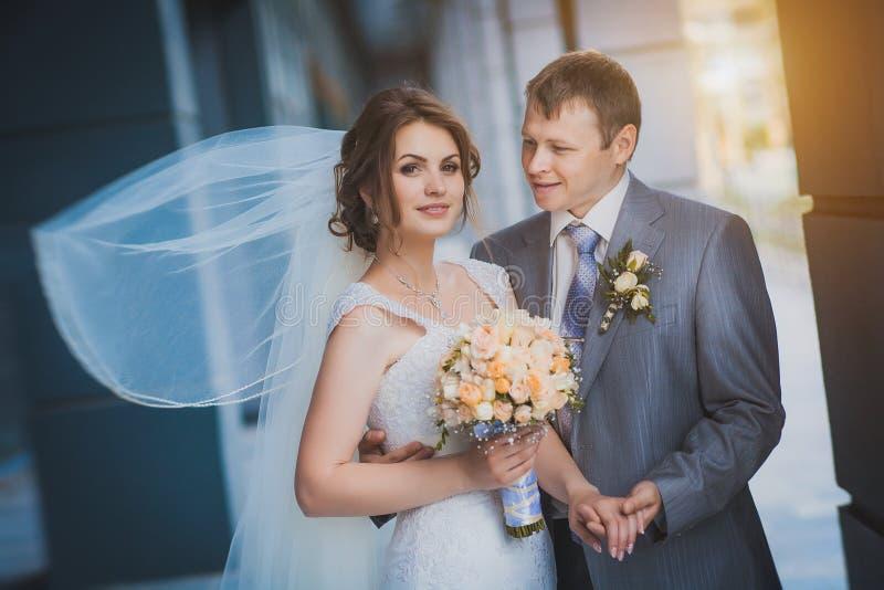 Gelukkige jonggehuwden tegen een blauw modern gebouw