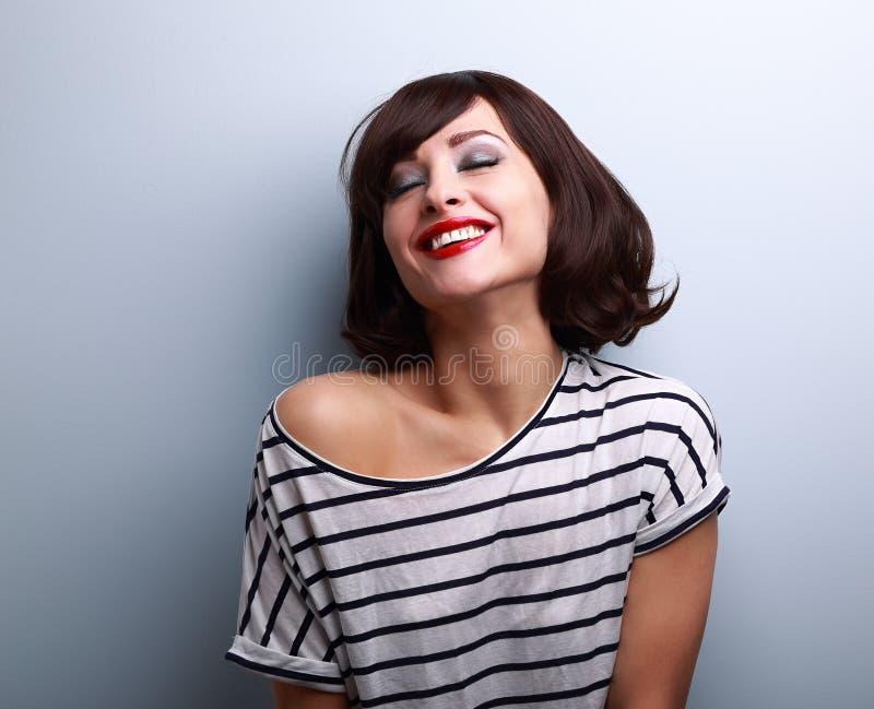 Gelukkige joying jonge vrouw met gesloten ogen op blauw royalty-vrije stock foto's