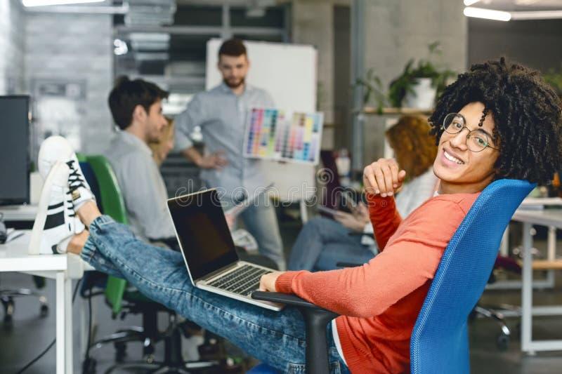 Gelukkige kalme glimlachende mens die rust na het oplossen van alle taken op het werk hebben stock afbeeldingen