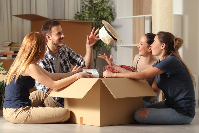 Gelukkige kamergenoten het gekscheren unboxing bezittingen die zich naar huis bewegen stock afbeelding
