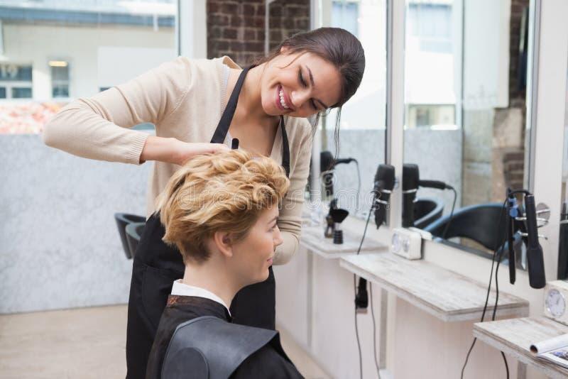 Gelukkige kapper die een klantenhaar snijden stock afbeeldingen