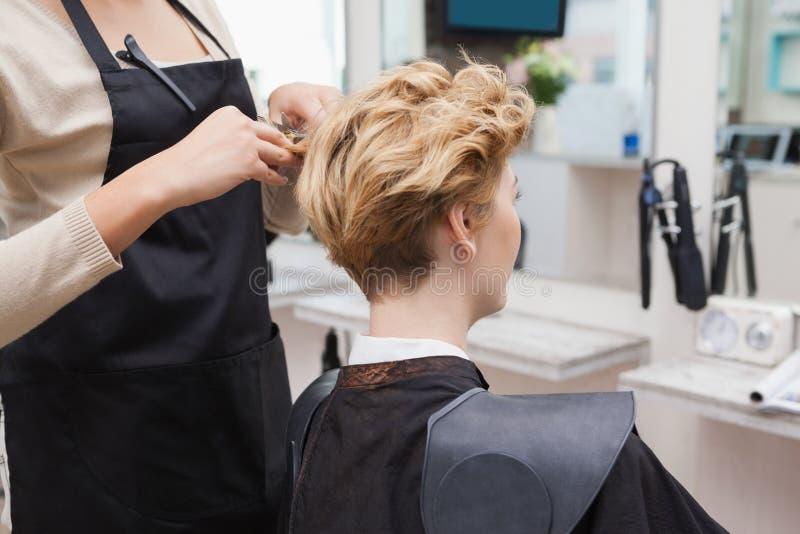 Gelukkige kapper die een klantenhaar snijden royalty-vrije stock foto's