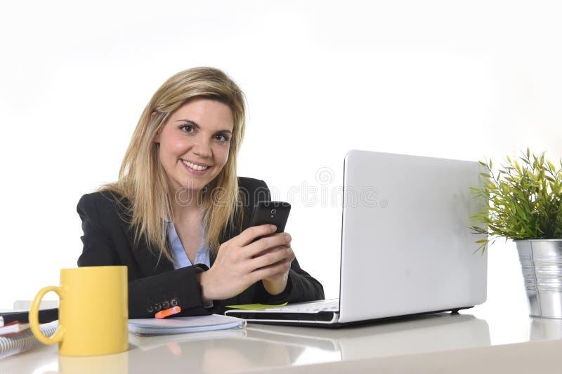 Gelukkige Kaukasische blonde bedrijfsvrouw die gebruikend mobiele telefoon bij het bureau van de bureaucomputer werken royalty-vrije stock afbeeldingen
