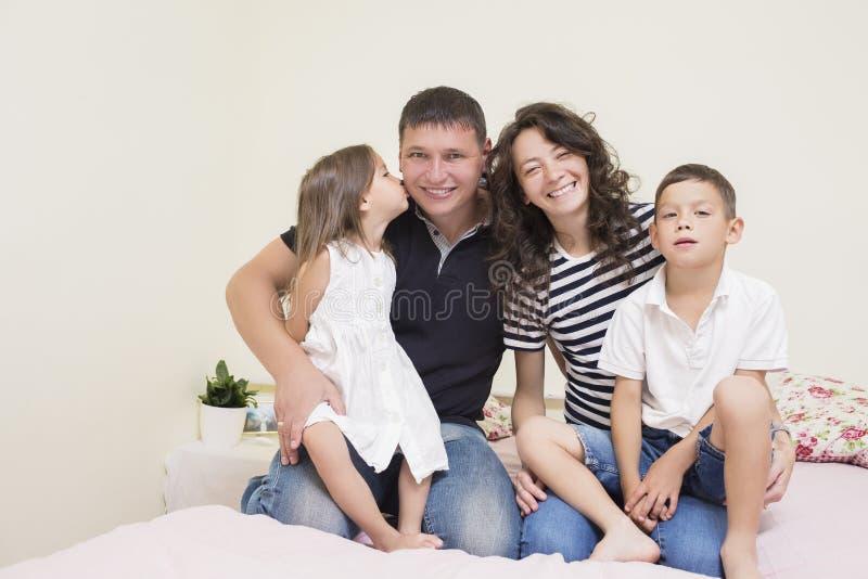 Gelukkige Kaukasische Familie die van Twee Ouder en Twee Jonge geitjes samen zitten stock afbeelding