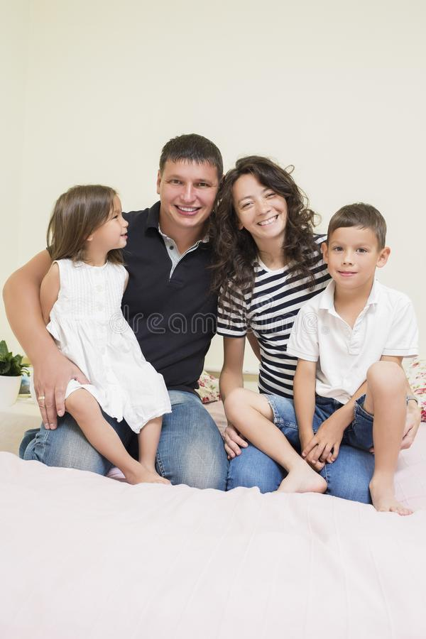 Gelukkige Kaukasische Familie van Twee Ouder en Twee Jonge geitjes samen Omhelst Zitten royalty-vrije stock foto's