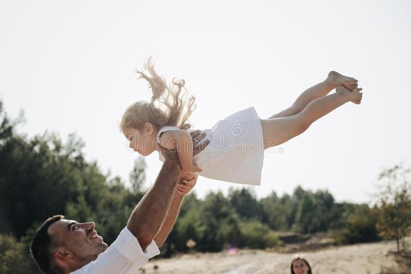 Gelukkige Kaukasische papa en zijn kleine dochter die pret hebben De vader werpt zoete dochter in witte kleding in de lucht stock foto