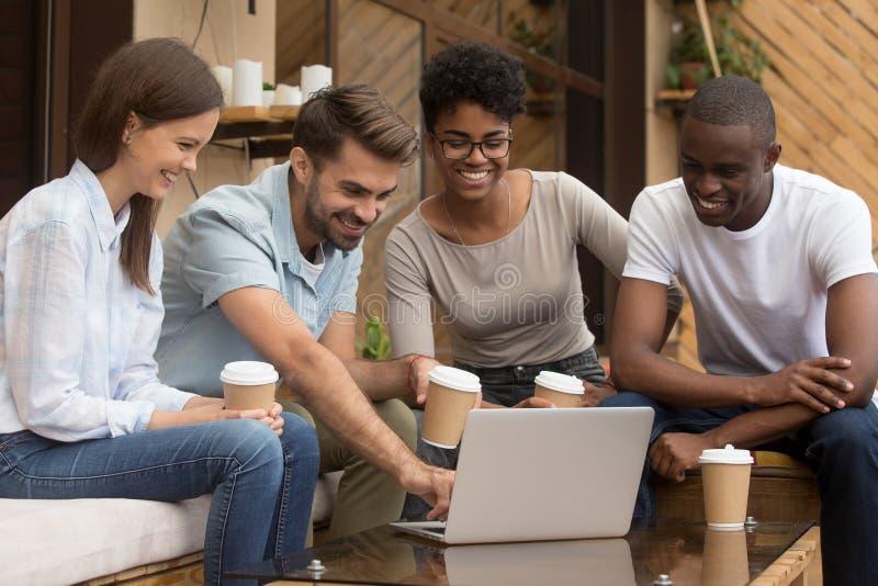 Gelukkige kerel die diverse vriendenvideo op laptop buiten coffeehouse tonen royalty-vrije stock foto