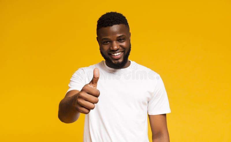 Gelukkige kerel die duim tonen en over gele achtergrond glimlachen stock afbeeldingen