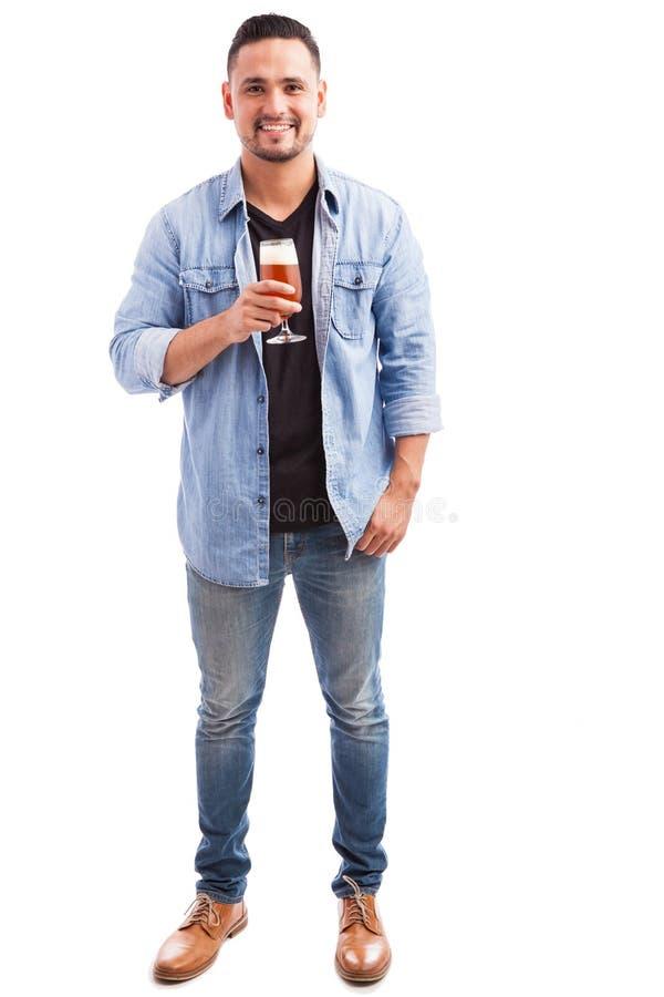 Gelukkige kerel die een glas bier drinken stock foto
