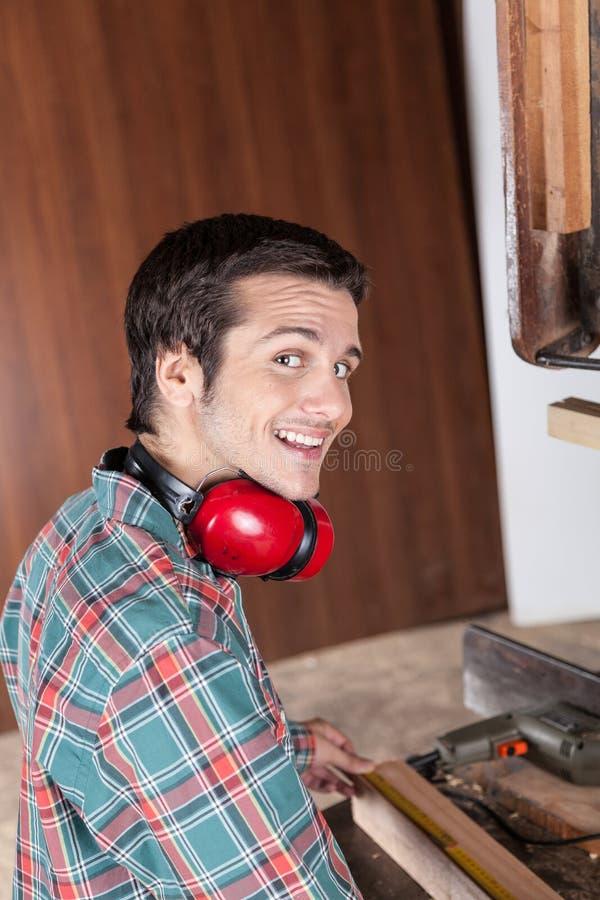 Gelukkige kerel die met hout werken stock foto's