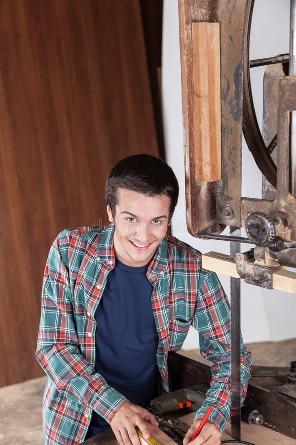 Gelukkige kerel die met hout werken stock afbeelding
