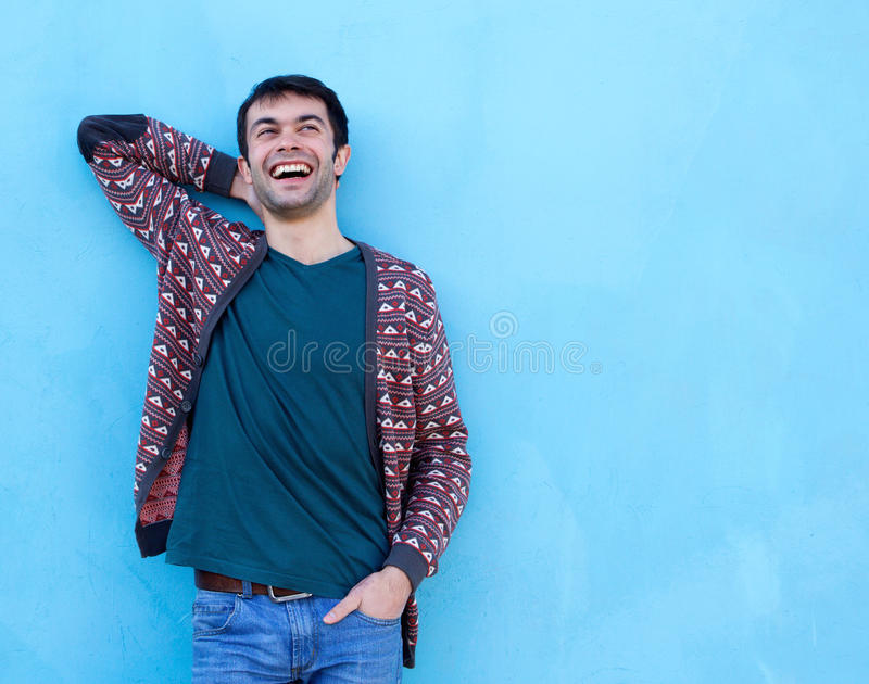 Gelukkige kerel die tegen blauwe achtergrond lachen royalty-vrije stock afbeelding