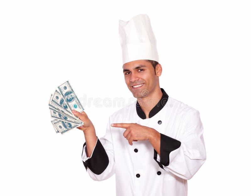 Gelukkige kerel in het contante geldgeld van de kok eenvormig holding stock afbeelding