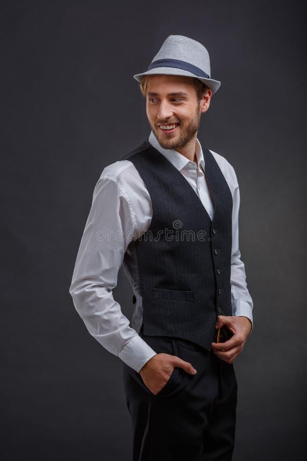 Gelukkige kerel in kostuum met vest en hoed, terug zijdelings stellend, kijkend en gelukkig glimlachend royalty-vrije stock afbeelding