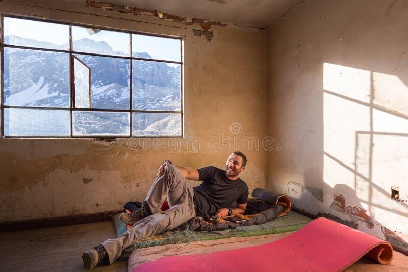Gelukkige kerelmens rustende het liggen het glimlachen oude ruimte verlaten matras onder de randmening van vensterbergen stock foto