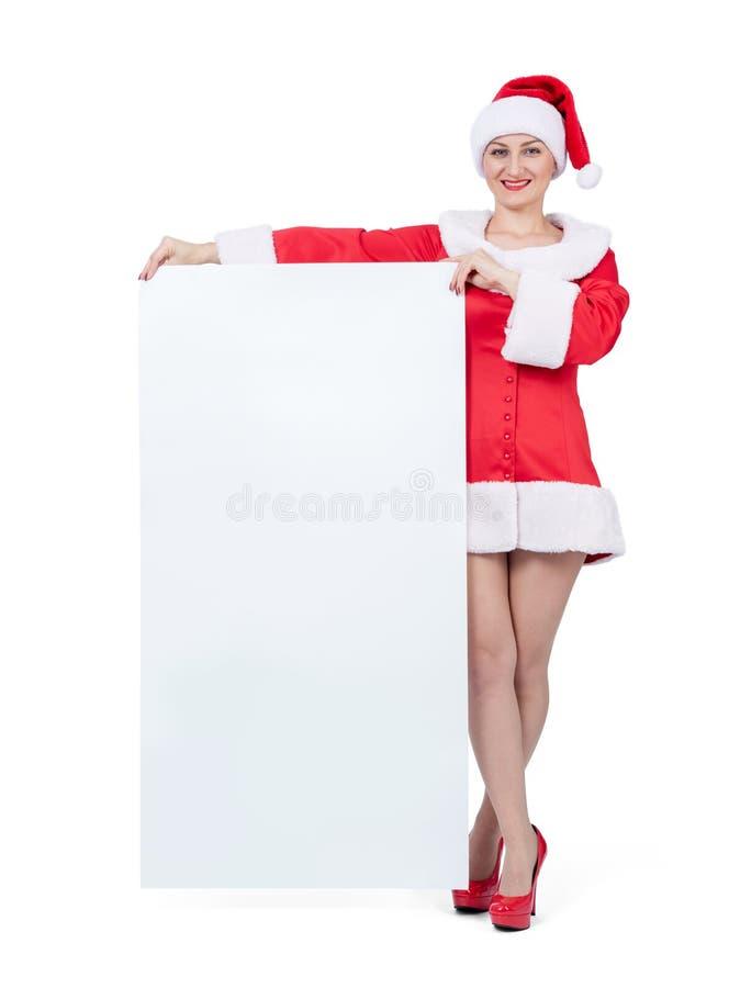 Gelukkige Kerstmanvrouw die grote witte verticale lege die banner houden, op witte achtergrond wordt geïsoleerd Het dossier bevat royalty-vrije stock fotografie
