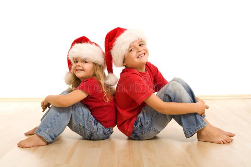Gelukkige Kerstmisjonge geitjes die op de vloer zitten royalty-vrije stock foto