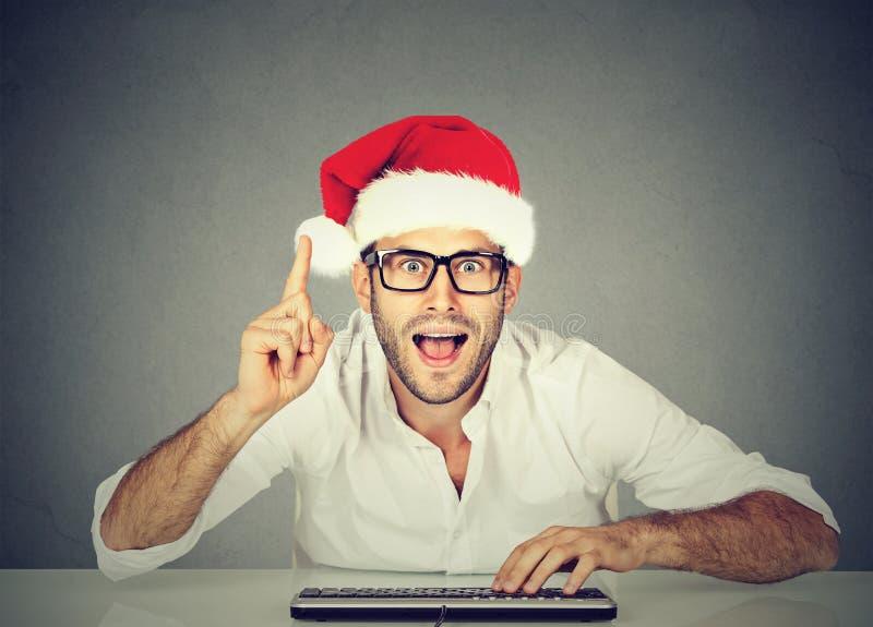 Gelukkige Kerstmismens in rood de hoed van de Kerstman het kopen materiaal online Vakantiekerstmis het winkelen royalty-vrije stock fotografie
