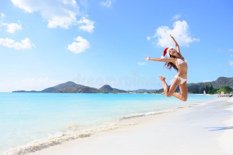 Gelukkige Kerstmisvakantie - meisje die op strand springen stock afbeeldingen