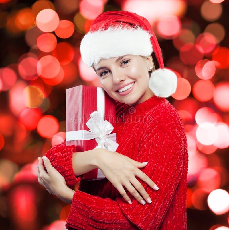 Gelukkige Kerstmisvrouw in Kerstmanhoed die pret met rode giftdoos hebben stock foto's