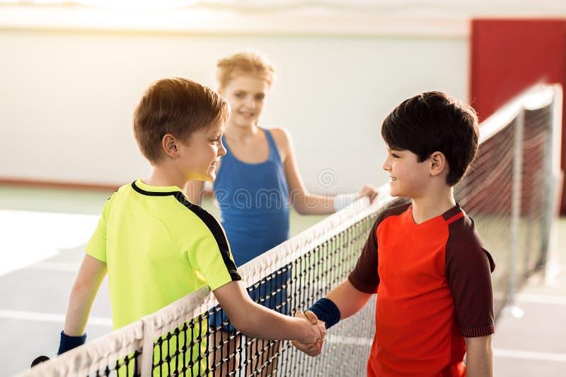 Gelukkige kinderen die de sportconcurrentie beëindigen door handdruk royalty-vrije stock foto's
