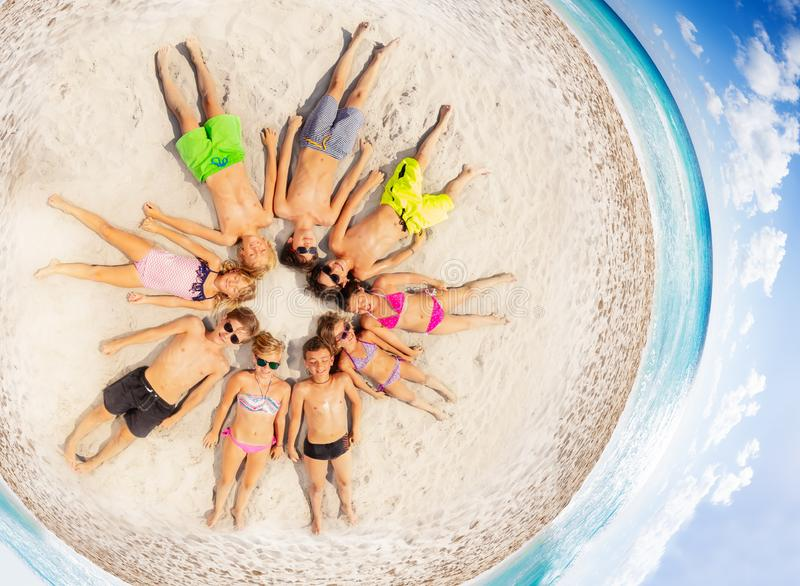 Gelukkige kinderen die in een cirkel op het strand leggen royalty-vrije stock afbeelding