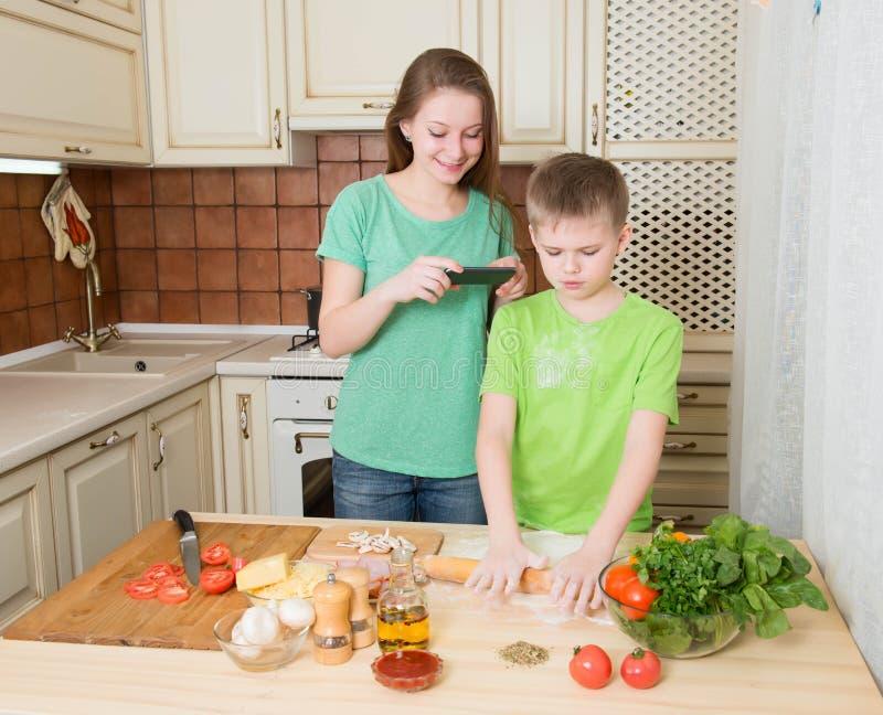 Gelukkige kinderen die eigengemaakte pizza thuis keuken koken tiener stock afbeeldingen